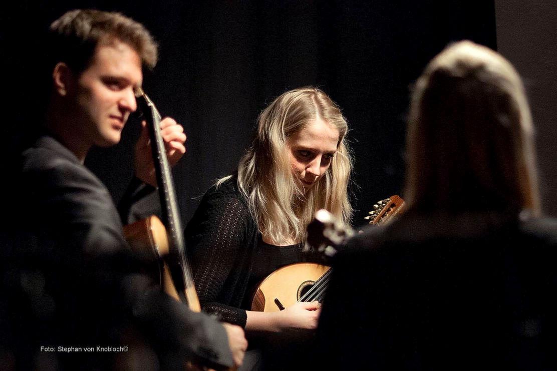 Das Ensemble Triologie im Konzert, links Markus Sich mit Gitarre, mitte Melanie Hilker mit Mandoline, rechts in der Rückansicht Kristina Lisner